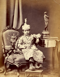 Full-length seated studio portrait of a young girl of an Indian princely family.